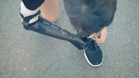 As sapatilhas os laços do ` que estão obtendo amarraram por um homem com uma mão protética