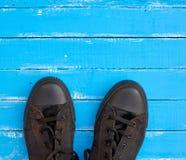 as sapatilhas velhas dos homens em uma superfície de madeira azul foto de stock