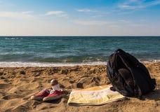 As sapatilhas vermelhas toalha e trouxa das sapatas sairam na praia pelo mar Funcione ao mar escape para um mergulho rápido foto de stock royalty free