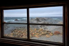 As Seen Through A Window, Broom Point, Newfoundland, Canada. Rugged seascape as viewed through the wooden window of a vintage fishing shanty at Broom Point, Gros stock photo