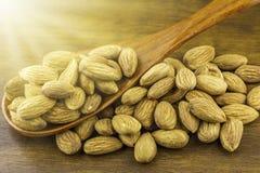 As sementes das amêndoas derramam da colher de madeira no fundo de madeira textured, vista superior Imagens de Stock Royalty Free