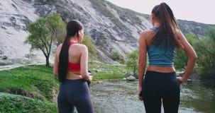 As senhoras atrativas com corpos aptos após um exercício de corrida cansado pararam para um bocado em opinião surpreendente da pa vídeos de arquivo
