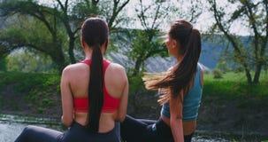 As senhoras bonitas em um sportswear após um exercício duro exercitam na natureza no lugar de surpresa da paisagem que apreciam o vídeos de arquivo