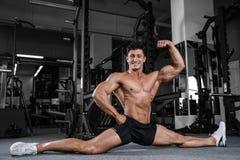 As separações esticam o homem que estica os pés na aptidão considerável do gym Foto de Stock Royalty Free