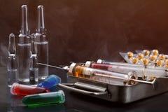 As seringas na caixa, nas ampolas e nos tubos de ensaio da esterilização com o líquido encoberto no vapor no fundo tonificaram pe Imagens de Stock Royalty Free