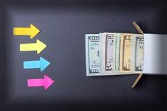 As setas apontam a uma pilha de notas de dólar que olham fora da caixa Aumente nas economias Cofre forte home Conceito do negócio foto de stock royalty free