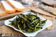As setas fritadas do alho com especiarias misturam e sementes de sésamo Setas verdes saborosos do alho em uma placa branca e em u Fotos de Stock