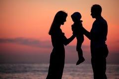 As silhuetas da família nas mãos de encontro ao mar declinam Imagens de Stock