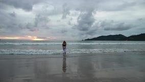 As silhuetas da menina do taanager que andam no verão encalham no por do sol filme
