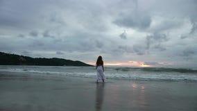 As silhuetas da menina do taanager que andam no verão encalham no por do sol vídeos de arquivo
