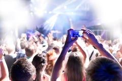 As silhuetas da multidão maciça no concerto do partido batem a música feliz Imagens de Stock Royalty Free