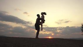 As silhuetas da raça misturada muscular atlética bonita acoplam fazer exercícios ginásticos no por do sol no pico de montanha filme