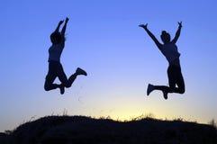 As silhuetas das duas meninas descreveram o salto foto de stock