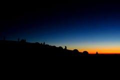 As silhuetas de barracas da formiga dos povos nas montanhas no por do sol iluminam-se Imagem de Stock