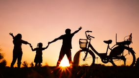 As silhuetas de famílias felizes jogam junto no parque no e fotografia de stock