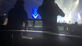 As silhuetas do concerto aglomeram-se na frente das luzes brilhantes da fase video estoque