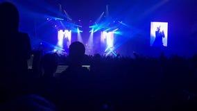 As silhuetas do concerto aglomeram-se na frente das luzes brilhantes da fase filme