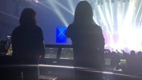 As silhuetas do concerto aglomeram-se na frente das luzes brilhantes da fase vídeos de arquivo