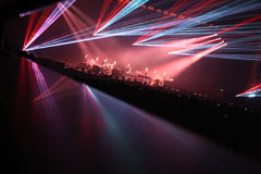 As silhuetas do concerto aglomeram-se na frente das luzes brilhantes da fase Fotos de Stock