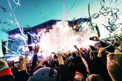 As silhuetas do concerto aglomeram-se na frente das luzes brilhantes da fase Fotografia de Stock