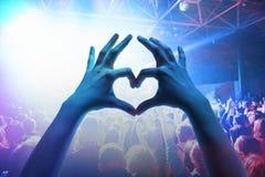 As silhuetas do concerto aglomeram-se na frente das luzes brilhantes da fase Foto de Stock Royalty Free