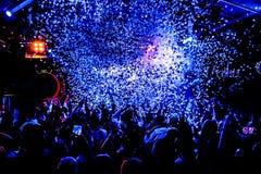 As silhuetas do concerto aglomeram-se na frente das luzes brilhantes da fase com confetes Fotos de Stock