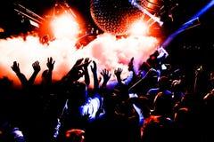 As silhuetas do concerto aglomeram-se na frente das luzes brilhantes da fase com confetes Imagem de Stock
