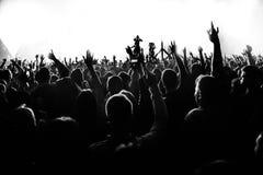 As silhuetas do concerto aglomeram-se na frente das luzes brilhantes da fase com confetes Fotografia de Stock Royalty Free