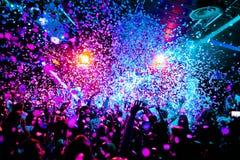 As silhuetas do concerto aglomeram-se na frente das luzes brilhantes da fase com confetes Imagens de Stock Royalty Free