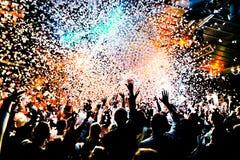As silhuetas do concerto aglomeram-se na frente das luzes brilhantes da fase com confetes Imagem de Stock Royalty Free