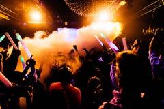 As silhuetas do concerto aglomeram-se na frente das luzes brilhantes da fase com confetes imagens de stock