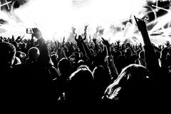 As silhuetas do concerto aglomeram-se na frente das luzes brilhantes da fase com confetes Foto de Stock Royalty Free