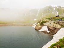 As silhuetas do lago depositam em montanhas alpinas, nuvens escuras pesadas da névoa estão vindo com forte vento Fotos de Stock Royalty Free