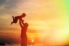 As silhuetas do pai e do filho jogam na praia Imagens de Stock Royalty Free