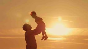 As silhuetas do pai e do filho jogam na praia do por do sol Imagens de Stock