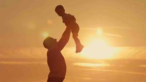 As silhuetas do pai e do filho jogam na praia do por do sol Foto de Stock Royalty Free