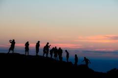 As silhuetas do pessoa do por do sol sobre um monte Fotos de Stock