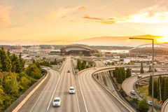As skylines de Seattle e as autoestrada de um estado a outro convirgem com Elliott Bay e o fundo no tempo do por do sol, Seattle  Imagens de Stock