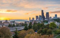 As skylines de Seattle e as autoestrada de um estado a outro convirgem com Elliott Bay e o fundo no tempo do por do sol, Seattle  Foto de Stock