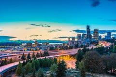 As skylines de Seattle e as autoestrada de um estado a outro convirgem com Elliott Bay e o fundo no tempo do por do sol, Seattle  Imagem de Stock
