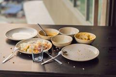As sobras do alimento nas placas, migalhas na tabela após o almoço o foto de stock royalty free