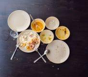 As sobras do alimento nas placas, nas migalhas na tabela após o almoço ou no jantar imagens de stock royalty free