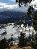 As sombras, as árvores, e as nuvens longas sobre a neve tamparam o estilo do retrato dos picos de montanha Foto de Stock Royalty Free