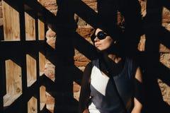As sombras caem através da porta na mulher perto da parede de tijolo Imagens de Stock