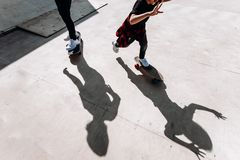 As sombras de dois homens que estão nos skates no assoalho em um parque do patim no dia ensolarado fora fotografia de stock