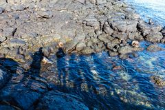 As sombras dos povos projetaram-se na água e nas rochas Fotografia de Stock