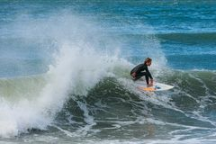 A surfer rides close to the lip of a breaking wave royalty free stock photography