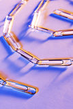 Only as strong as the weakest link. Still life of a chain of paperclips with blue and orange lighting Stock Images