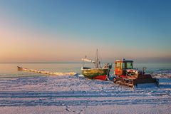 The sun set over the sea. As the sun set over the sea stands in a boat and tractor Royalty Free Stock Image
