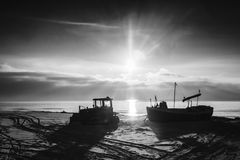 The sun set over the sea. As the sun set over the sea stands in a boat and tractor Stock Image
